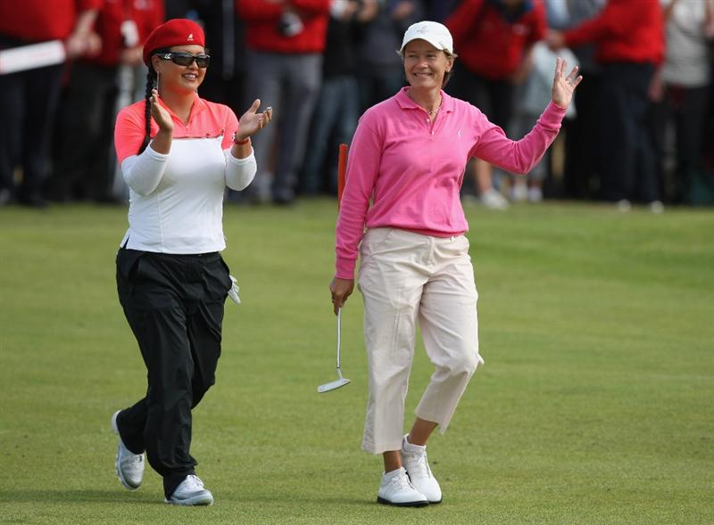 LYTHAM ST ANNES, ENGLAND - AUGUST 02:  Catriona Matthew of Scotland acknowledges the crowd on the 18th green with Christina Kim (L) of USA on her way to victory during the final round of the 2009 Ricoh Women's British Open Championship held at Royal Lytham St Annes Golf Club, on August 2, 2009 in Lytham St Annes, England.  (Photo by David Cannon/Getty Images)