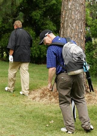 SYDNEY, AUSTRALIA - DECEMBER 11:  Spectator Brad Clegg (R) looks for his camera after it was thrown against a tree by John Daly (L) of the USA on the ninth hole during the first round of the 2008 Australian Open at The Royal Sydney Golf Club on December 11, 2008 in Sydney, Australia.  (Photo by Mark Nolan/Getty Images)