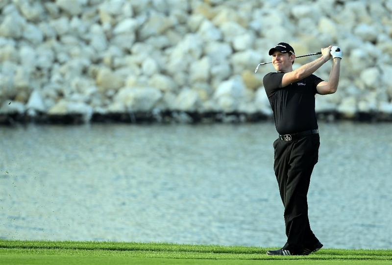 BAHRAIN, BAHRAIN - JANUARY 30:  Stephen Gallacher of Scotland plays his second shot at the 18th hole during the final round of the 2011 Volvo Champions held at the Royal Golf Club on January 30, 2011 in Bahrain, Bahrain.  (Photo by David Cannon/Getty Images)