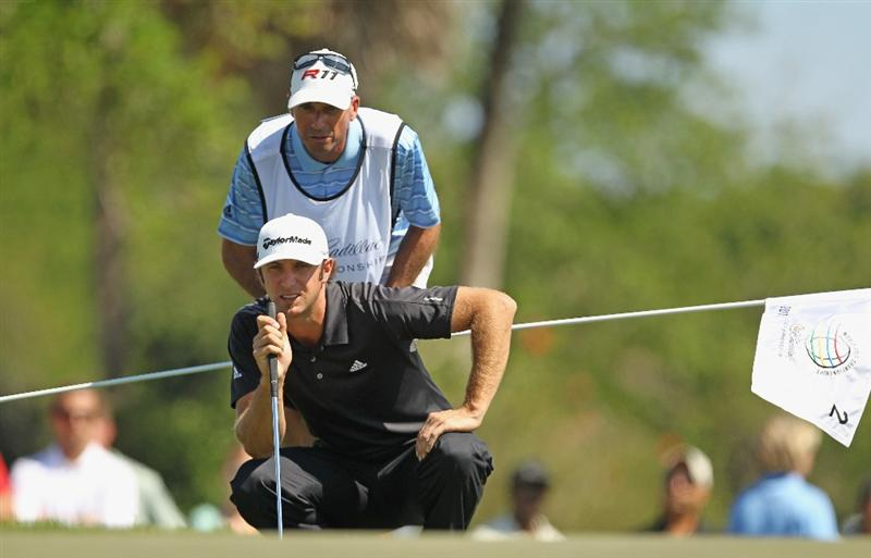 DORAL, FL - MARCH 13:  Dustin Johnson lines up a putt on the second green with his caddie Bobby Brown during the final round of the 2011 WGC- Cadillac Championship at the TPC Blue Monster at the Doral Golf Resort and Spa on March 13, 2011 in Doral, Florida.  (Photo by Mike Ehrmann/Getty Images)