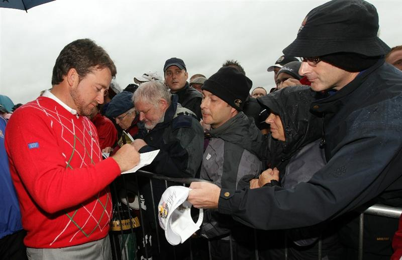 NEWPORT, WALES - OCTOBER 01:  Graeme McDowell of Europe signs autographs as rain falls and play is suspended during the Morning Fourball Matches during the 2010 Ryder Cup at the Celtic Manor Resort on October 1, 2010 in Newport, Wales.  (Photo by Andrew Redington/Getty Images)