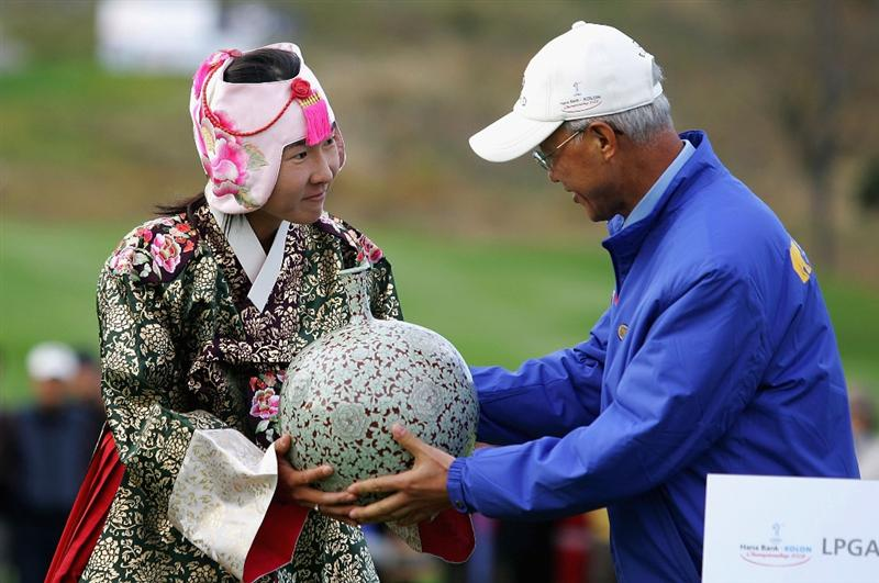 INCHEON, SOUTH KOREA - NOVEMBER 02:  Candie Kung of Chinese Taipei lifts the winners trophy as she wears a South Korean traditional costume and crown during a ceremony following the Hana Bank KOLON Championship at Sky72 Golf Club on November 2, 2008 in Incheon, South Korea. Kung finished the three round with a course record 6 under par.  (Photo by Chung Sung-Jun/Getty Images)