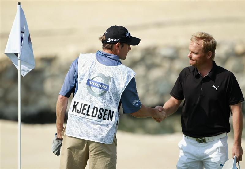 BAHRAIN, BAHRAIN - JANUARY 30:  Soren Kjeldesn of Denmark is congratulated by hs caddie on the 18th green after shooting 63 during the final round of the Volvo Golf Champions at The Royal Golf Club on January 30, 2011 in Bahrain, Bahrain.  (Photo by Andrew Redington/Getty Images)
