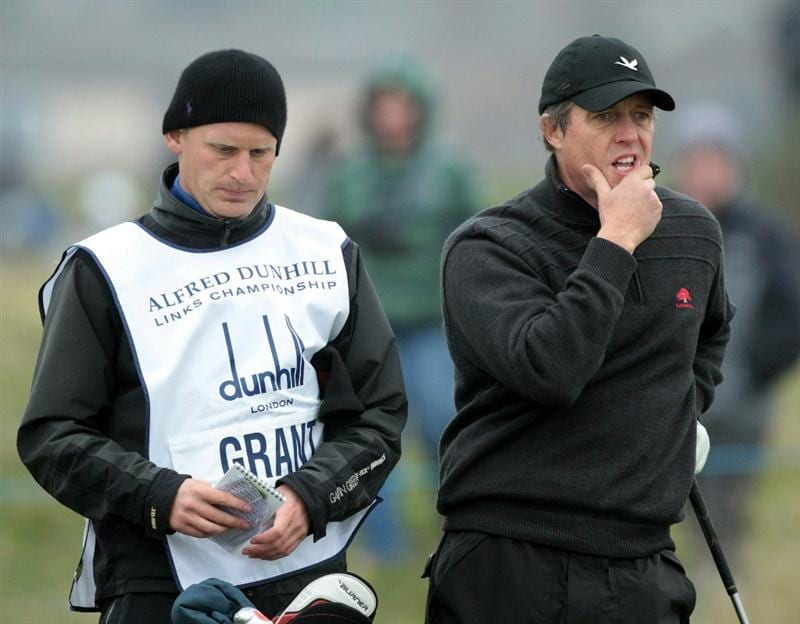 CARNOUSTIE, SCOTLAND - OCTOBER 09:  Hollywood actor Hugh Grant with his caddie on the first hole during the third round of The Alfred Dunhill Links Championship at the Carnoustie Golf Links on October 9, 2010 in Carnoustie, Scotland.  (Photo by David Cannon/Getty Images)