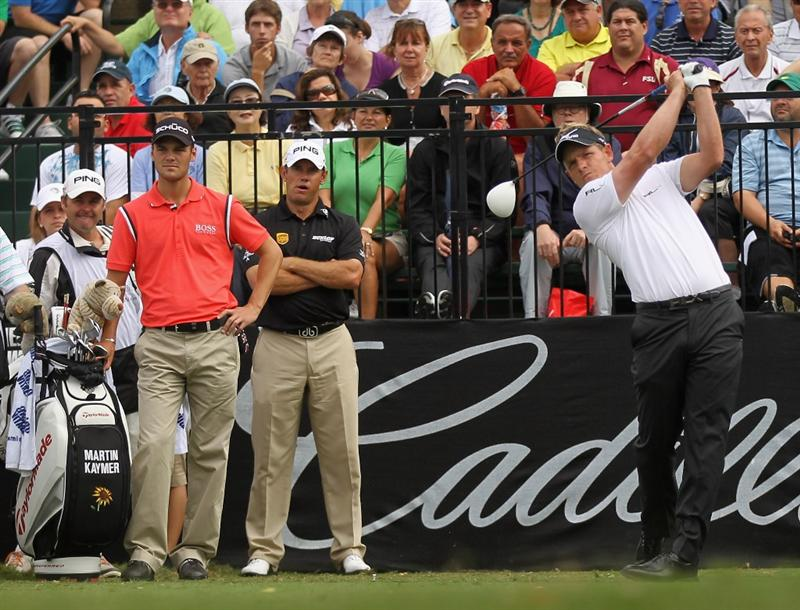 DORAL, FL - MARCH 10:  Luke Donald of England (R) hits his tee shot on the first hole as Martin Kaymer and Lee Westwood look on during the first round of the 2011 WGC- Cadillac Championship at the TPC Blue Monster at the Doral Golf Resort and Spa on March 10, 2011 in Doral, Florida.  (Photo by Mike Ehrmann/Getty Images)