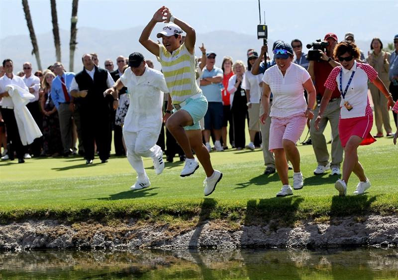 RANCHO MIRAGE, CA - APRIL 04:  Champion Yani Tseng of Taiwan  jumps in the lake surrounding the 18th green after the final round of the Kraft Nabisco Championship at Mission Hills Country Club on April 4, 2010 in Rancho Mirage, California.  (Photo by Stephen Dunn/Getty Images)