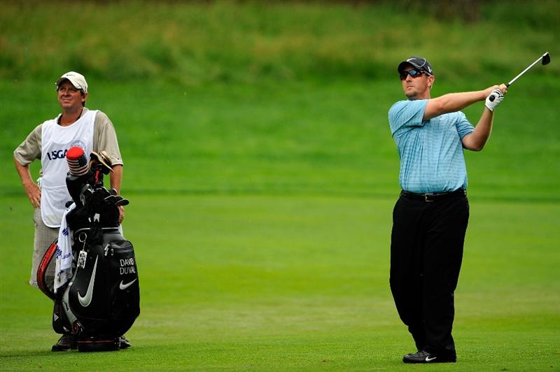 FARMINGDALE, NY - JUNE 21:  David Duval hits a shot from the fairway on the second hole while his caddie Jeff Weber looks on during the continuation of the third round of the 109th U.S. Open on the Black Course at Bethpage State Park on June 21, 2009 in Farmingdale, New York.  (Photo by Sam Greenwood/Getty Images)