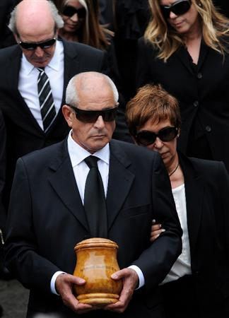 PEDRENA, SPAIN - MAY 11:  Baldomero Ballesteros (L) carries the urn containing the ashes of his brother Seve Ballesteros besides his wife Carmen Cabarga during the funeral service held for the legendary Spanish golfer on May 11, 2011 in Pedrena, Spain. Top-ranked golf players have joined family members and friends to pay their last respects to the late golf great, who died on May 7, 2011 from complications arising from a brain tumor, in his home town parish church.  (Photo by Jasper Juinen/Getty Images)