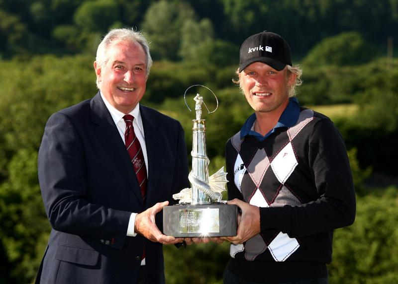 NEWPORT, WALES - JUNE 07:  Jeppe Huldahl of Denmark poses with the trophy and 2010 Course Captain and Welsh rugby legend Gareth Edwards after the final round of the Celtic Manor Wales Open on the 2010 Course at The Celtic Manor Resort on June 7, 2009 in Newport, Wales.  (Photo by Richard Heathcote/Getty Images)