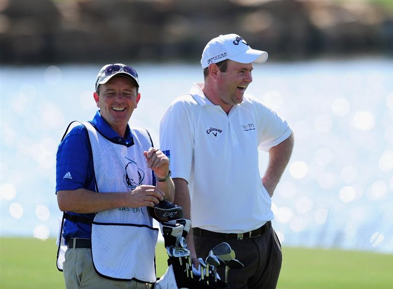 VILAMOURA, PORTUGAL - OCTOBER 15:  Alastair Forsyth of Scotland and caddie share a joke on the 18th hole during the first round of the Portugal Masters at the Oceanico Victoria Golf Course on October 15, 2009 in Vilamoura, Portugal.  (Photo by Stuart Franklin/Getty Images)