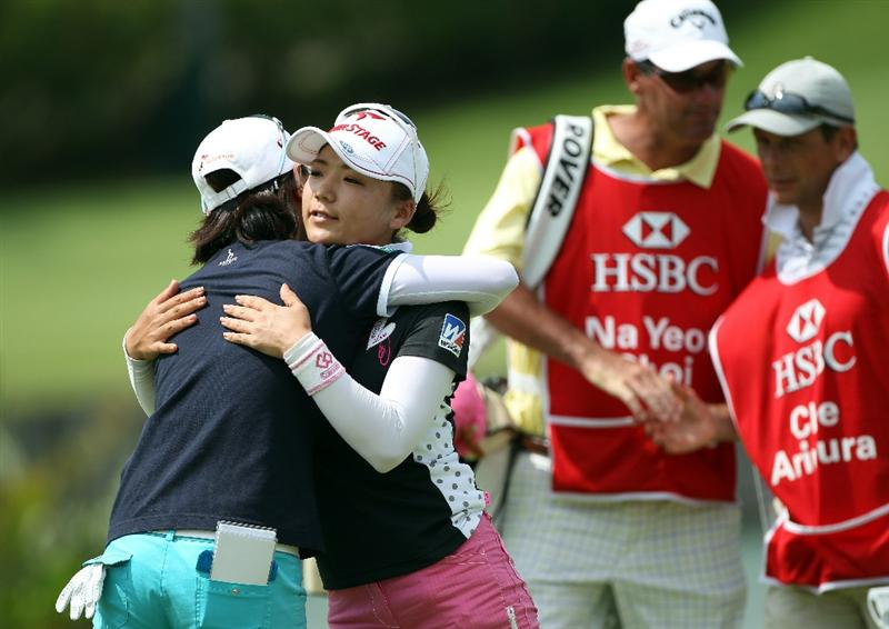 SINGAPORE - FEBRUARY 25:  Chie Arimura of Japan (second from left) embraces Na Yeon Choi of South Korea on the 18th hole as their caddies look on during the second round of the HSBC Women's Champions at the Tanah Merah Country Club on February 25, 2011 in Singapore.  (Photo by Andrew Redington/Getty Images)