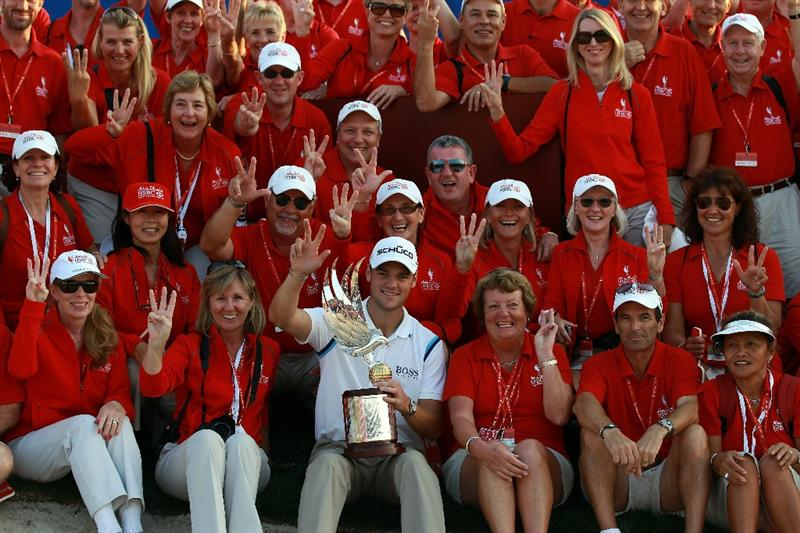 ABU DHABI, UNITED ARAB EMIRATES - JANUARY 23:  Martin Kaymer of Germany holds the trophy in amongst a group of tournament marshalls after winning the 2011 Abu Dhabi HSBC Golf Championship held at the Abu Dhabi Golf Club on January 23, 2011 in Abu Dhabi, United Arab Emirates.  (Photo by David Cannon/Getty Images)