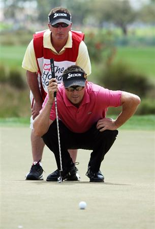 PALM BEACH GARDENS, FL - MARCH 08:  Robert Allenby of Australia and his caddie line up a birdie putt on the third hole during the final round of The Honda Classic at PGA National Resort and Spa on March 8, 2009 in Palm Beach Gardens, Florida.  (Photo by Doug Benc/Getty Images)