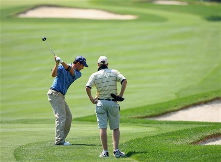 AKRON, OH - JULY 29:  Padraig Harrington of Ireland plays an approach shot whilst being watched by his caddie Ronan Flood during practice for the World Golf Championship Bridgestone Invitational at Firestone Country Club on July 29, 2008 in Akron, Ohio.  (Photo by Stuart Franklin/Getty Images)