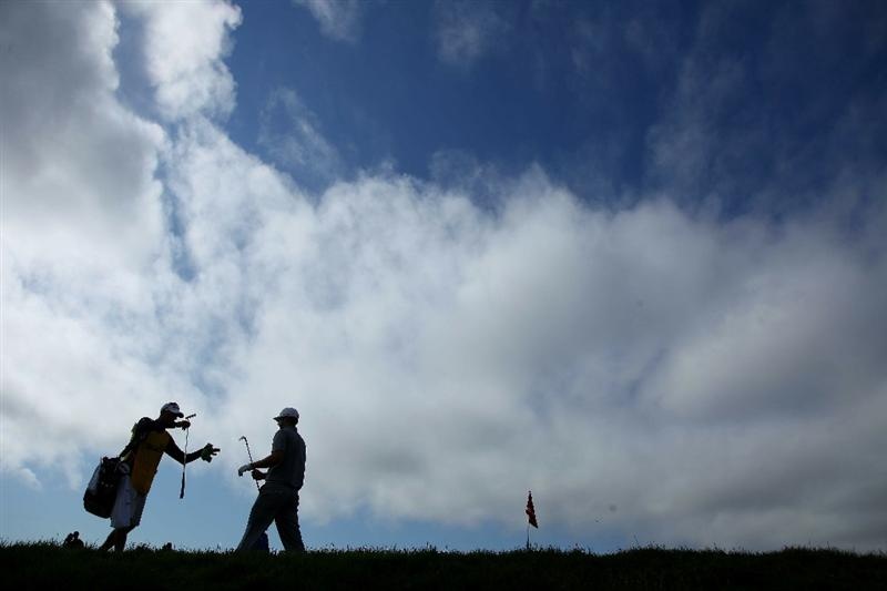 PEBBLE BEACH, CA - JUNE 19:  Dustin Johnson grabs his putter from his caddie Bobby Brown on the eigth hole during the third round of the 110th U.S. Open at Pebble Beach Golf Links on June 19, 2010 in Pebble Beach, California.  (Photo by Donald Miralle/Getty Images)