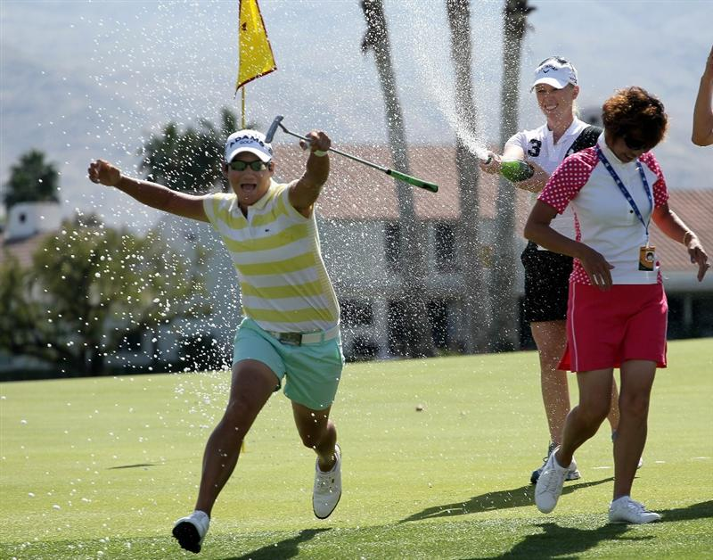RANCHO MIRAGE, CA - APRIL 4: Champion Yani Tseng of Taiwan runs as Morgan Pressel sprays her with Champaign on the 18th green after the final round of the Kraft Nabisco Championship at Mission Hills Country Club on April 4, 2010 in Rancho Mirage, California.  (Photo by Stephen Dunn/Getty Images)