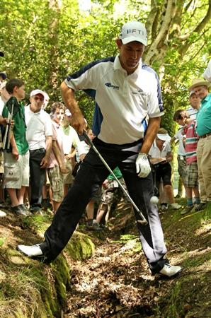 VIRGINIA WATER, ENGLAND - MAY 23:  Padraig Harrington of Ireland retrieves his ball from a ditch on the 3rd hole during the final round of the BMW PGA Championship on the West Course at Wentworth on May 23, 2010 in Virginia Water, England.  (Photo by Warren Little/Getty Images)