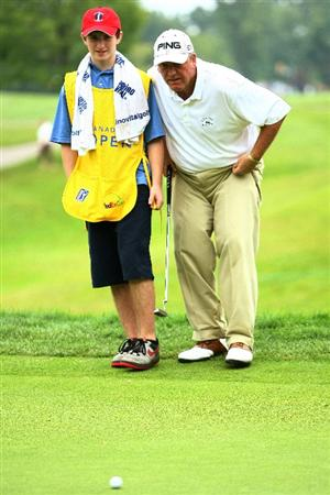 OAKVILLE, ONTARIO - JULY 25:  Mark Calcavecchia lines up a putt with his caddie, son Eric Calcavecchia on the ninth green during round two of the RBC Canadian Open at Glen Abbey Golf Club on July 25, 2009 in Oakville, Ontario, Canada.  (Photo by Chris McGrath/Getty Images)