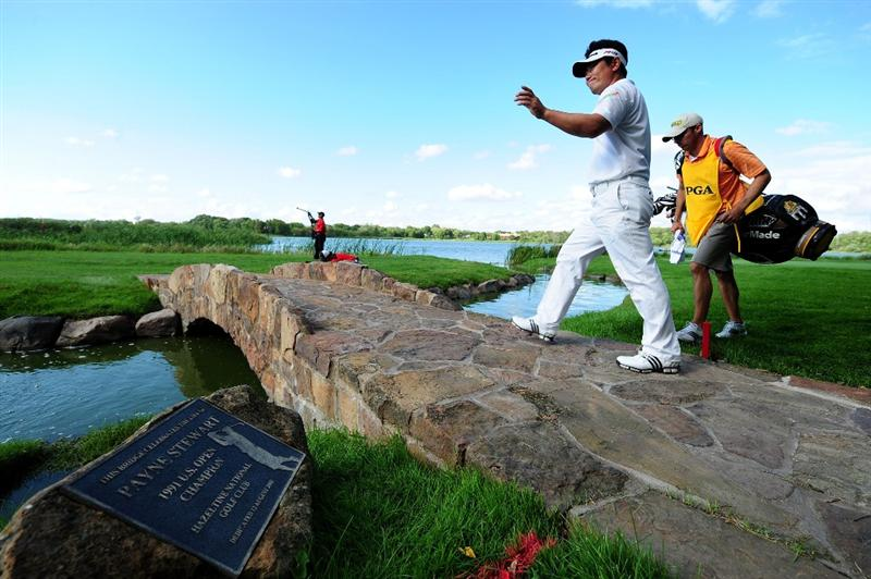CHASKA, MN - AUGUST 16:  Y.E. Yang of South Korea (L) crosses a bridge on the 16th hole with his caddie A.J. Montecinos during the final round of the 91st PGA Championship at Hazeltine National Golf Club on August 16, 2009 in Chaska, Minnesota.  (Photo by Stuart Franklin/Getty Images)