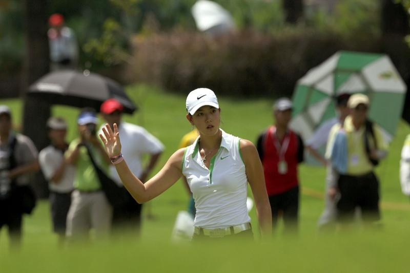 KUALA LUMPUR, MALAYSIA - OCTOBER 22 : Michelle Wie of the USA waves to the crowd after a bunker shot on the 3rd hole during Round One of the Sime Darby LPGA on October 22, 2010 at the Kuala Lumpur Golf and Country Club in Kuala Lumpur, Malaysia. (Photo by Stanley Chou/Getty Images)