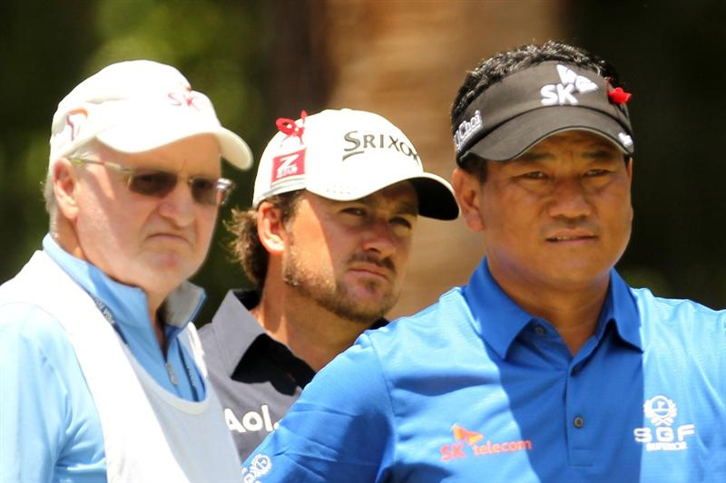 PONTE VEDRA BEACH, FL - MAY 15:  (L-R) Caddie Andy Prodger, Graeme McDowell of Northern Ireland and K.J. Choi of South Korea look on from the second tee during the final round of THE PLAYERS Championship held at THE PLAYERS Stadium course at TPC Sawgrass on May 15, 2011 in Ponte Vedra Beach, Florida.  (Photo by Mike Ehrmann/Getty Images)