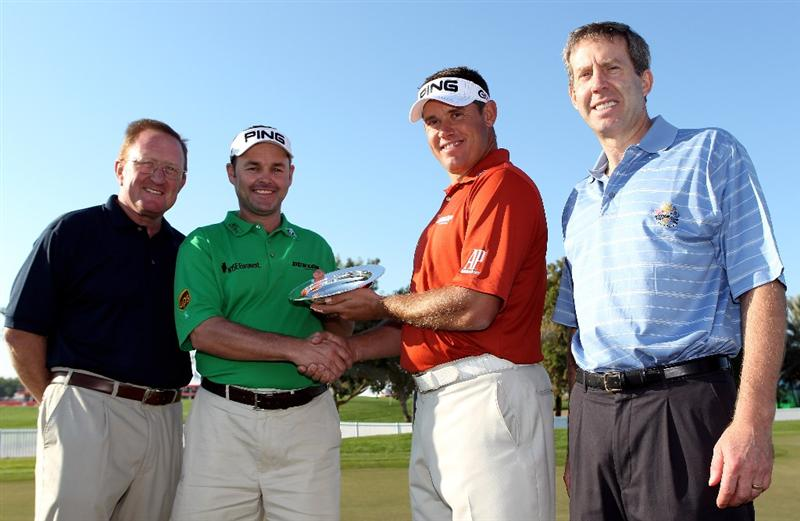 ABU DHABI, UNITED ARAB EMIRATES - JANUARY 19:  Lee Westwood of England (2nd R) presents his caddie Billy Foster with a European Tour special award for his role in helping Westwood win the 2009 Race To Dubai as Richard Hills, Ryder Cup Director, (L) and Keith Waters, European Tour Director for International Policy, (R) look on during a photocall at The Abu Dhabi Golf Championship at Abu Dhabi Golf Club on January 19, 2010 in Abu Dhabi, United Arab Emirates.  (Photo by Andrew Redington/Getty Images)
