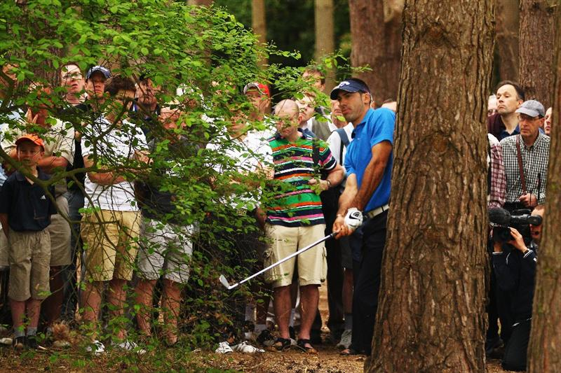 VIRGINIA WATER, ENGLAND - MAY 20:  Alvaro Quiros of Spain plays an iron shot from the trees at the 12th hole during the first round of the BMW PGA Championship on the West Course at Wentworth on May 20, 2010 in Virginia Water, England.  (Photo by Richard Heathcote/Getty Images)