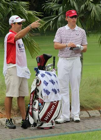 KUALA LUMPUR, MALAYSIA - OCTOBER 30: Ricky Barnes of USA and his caddie discuss a point on the rough of the 13th hole during day three of the CIMB Asia Pacific Classic at The MINES Resort & Golf Club on October 30, 2010 in Kuala Lumpur, Malaysia. (Photo by Stanley Chou/Getty Images)