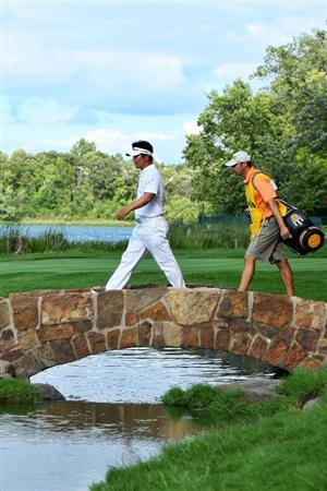 CHASKA, MN - AUGUST 16:  Y.E. Yang of South Korea (L) crosses a bridge on the 16th hole with his caddie A.J. Montecinos during the final round of the 91st PGA Championship at Hazeltine National Golf Club on August 16, 2009 in Chaska, Minnesota.  (Photo by Streeter Lecka/Getty Images)