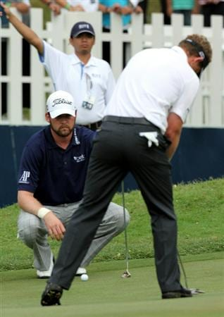 KUALA LUMPUR, MALAYSIA - OCTOBER 30: Luke Donald of England putts while T.J.Trahan of USA looks on on  the 18th hole during day three of the CIMB Asia Pacific Classic at The MINES Resort & Golf Club on October 30, 2010 in Kuala Lumpur, Malaysia. (Photo by Stanley Chou/Getty Images)