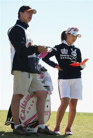 PHOENIX - MARCH 27:  Caddie Terry McNamara (L) gives instructions to Momoko Ueda of Japan on the 15th hole fairway during the second round of the J Golf Phoenix LPGA International golf tournament at Papago Golf Course on March 27, 2009 in Phoenix, Arizona.  (Photo by Christian Petersen/Getty Images)