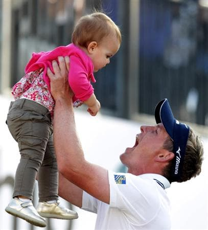 VIRGINIA WATER, ENGLAND - MAY 29:  Luke Donald of England lifts up his daughter Elle following his victory in a playoff on the 18th green during the final round of the BMW PGA Championship  at the Wentworth Club on May 29, 2011 in Virginia Water, England.  (Photo by Ross Kinnaird/Getty Images)