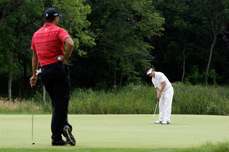 CHASKA, MN - AUGUST 16:  Y.E. Yang of South Korea (R) putts on the tenth hole while Tiger Woods looks on during the final round of the 91st PGA Championship at Hazeltine National Golf Club on August 16, 2009 in Chaska, Minnesota.  (Photo by Jamie Squire/Getty Images)