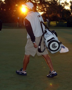 A caddy crosses the practice putting green at sunrise before  the Progress Energy Partner Pro-Am on the Copperhead Course before the 2005 Chrysler Championship October 26 in Palm Harbor, Florida.Photo by Al Messerschmidt/WireImage.com
