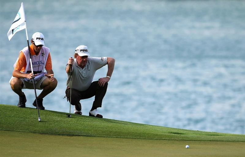 SINGAPORE - NOVEMBER 12: Miguel Angel Jimenez of Spain and his caddie check a line before play on the 7th hole during the second round of the Barclays Singapore Open held at the Sentosa Golf Club on November 12, 2010 in Singapore, Singapore.  (Photo by Stanley Chou/Getty Images)