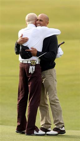 ST ANDREWS, SCOTLAND - OCTOBER 05:  Simon Dyson of England is congratulated by his playing partner US surfing champion Kelly Slater on the 18th green after victory at the The Alfred Dunhill Links Championship at The Old Course on October 5, 2009 in St.Andrews, Scotland.  (Photo by Andrew Redington/Getty Images)