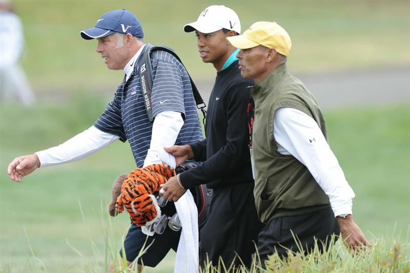 PEBBLE BEACH, CA - JUNE 18:  Tiger Woods (C) walks off the ninth green alongside his caddie Steve Williams (L) and fomer NFL head coach Herman Edwards  during the second round of the 110th U.S. Open at Pebble Beach Golf Links on June 18, 2010 in Pebble Beach, California.  (Photo by Harry How/Getty Images)