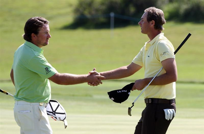CASARES, SPAIN - MAY 21:  Nicolas Colsaerts of Belgium is congratulated by Graeme McDowell of Northern Ireland after his quarter final match of the Volvo World Match Play Championships at Finca Cortesin on May 20, 2011 in Casares, Spain.  (Photo by Ross Kinnaird/Getty Images)