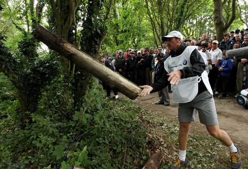 VIRGINIA WATER, ENGLAND - MAY 29:  Luke Donald's caddie John McLaren removes a log on the 1st hole during the final round of the BMW PGA Championship  at the Wentworth Club on May 29, 2011 in Virginia Water, England.  (Photo by Warren Little/Getty Images)