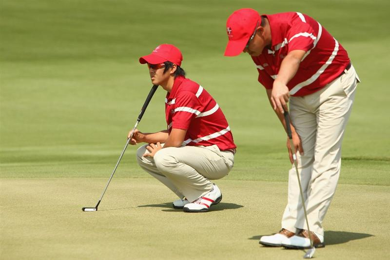 BANGKOK, THAILAND - JANUARY 09:  Ryo Lshikawa of Japan lines up a put with Toru Taniguchi of Japan during the foursomes on Day one of The Royal Trophy at the Amata Spring Country Club on January 9, 2009 in Bangkok, Thailand.  (Photo by Ian Walton/Getty Images)