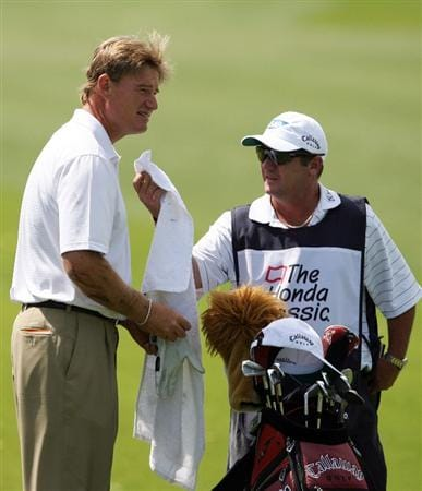 PALM BEACH GARDENS, FL - MARCH 05: Ernie Els wipes mud off his hands as his caddie hands him a towel after Els opted to hit out of the water hazard on the sixth fairway during the first round of The Honda Classic at PGA National Resort and Spa on March 5, 2009 in Palm Beach Gardens, Florida.  (Photo by Doug Benc/Getty Images)