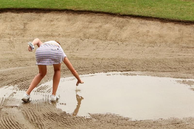GOLD COAST, AUSTRALIA - MARCH 06:  Florentyna Parker of England picks her ball out of a flooded bunker on the 2nd hole during round three of the 2010 ANZ Ladies Masters at Royal Pines Resort on March 6, 2010 in Gold Coast, Australia.  (Photo by Ryan Pierse/Getty Images)