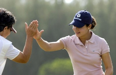Lorena Ochoa high fives a playing partner after a birdie putt on the 18th green during the pro am at the 2006 SBS Open at Turtle Bay February 15 at Kahuku, Hawaii.Photo by Al Messerschmidt/WireImage.com