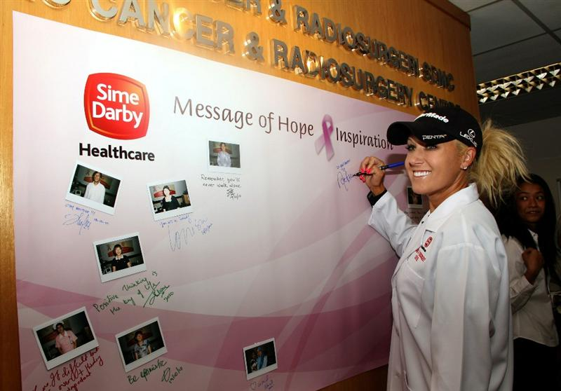 KUALA LUMPUR, MALAYSIA - OCTOBER 19 : Natalie Gulbis of USA signs her autograph on the message of hope for cancer board during the Sime Darby LPGA Charity visit to the Subang Medical Centre on October 19, 2010 in Kuala Lumpur, Malaysia (Photo by Stanley Chou/Getty Images)