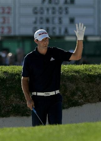 PEBBLE BEACH, CA - FEBRUARY 14:  Dustin Johnson waves after hitting out of the bunker on the 18th hole during the final round of the AT&T Pebble Beach National Pro-Am at Pebble Beach Golf Links on February 14, 2010 in Pebble Beach, California. (Photo by Stephen Dunn/Getty Images)