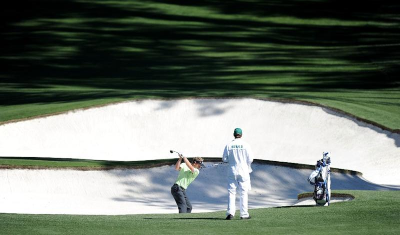 AUGUSTA, GA - APRIL 06:  Luke Donald of England plays a bunker shot as his caddie John McLaren looks on during a practice round prior to the 2011 Masters Tournament at Augusta National Golf Club on April 6, 2011 in Augusta, Georgia.  (Photo by Harry How/Getty Images)