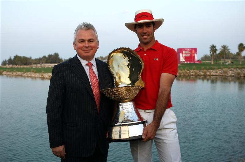 DOHA, QATAR - JANUARY 25:  Alvaro Quiros of Spain is presented with the trophy by Andrew Stevens of Commercialbank after winning the Commercialbank Qatar Masters at Doha Golf Club on January 25, 2009 in Doha, Qatar.  (Photo by Andrew Redington/Getty Images)
