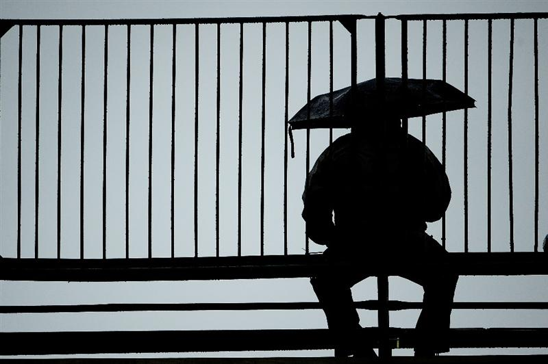 FARMINGDALE, NY - JUNE 18:  A spectator waits under an umbrella in a grandstand during the first round of the 109th U.S. Open on the Black Course at Bethpage State Park on June 18, 2009 in Farmingdale, New York.  (Photo by Sam Greenwood/Getty Images)