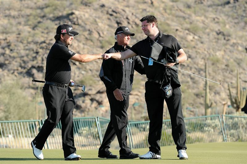 MARANA, AZ - FEBRUARY 24:  Graeme McDowell of Northern Ireland (L) is seen with manager Conor Ridge (R) and coach Pete Cowan (C) on the practice range during the second round of the Accenture Match Play Championship at the Ritz-Carlton Golf Club on February 24, 2011 in Marana, Arizona.  (Photo by Stuart Franklin/Getty Images)