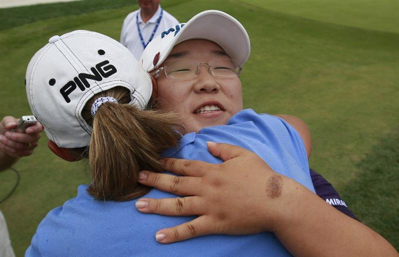 ROGERS, AR - SEPTEMBER 13:  Jiyai Shin of South Korea hugs Angela Stanford (back to camera) after making a birdie on the second playoff hole to win the P&G Beauty NW Arkansas Championship at the Pinnacle Country Club on September 13, 2009 in Rogers, Arkansas.  (Photo by Dave Martin/Getty Images)